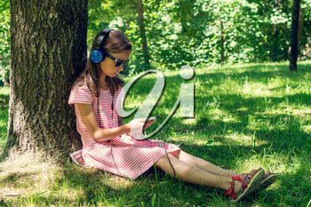 Girl listening to music under the tree shadow