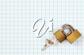 Two linked padlocks lying on squared paper background