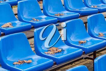 Empty plastic seats at small city stadium during autumn season