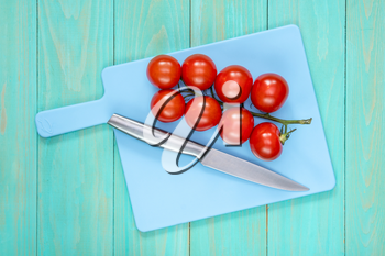 The branch of tomatoes and knife on a blue cutting board