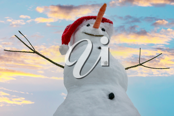 Funny snowman in Santa hat with sky background.
