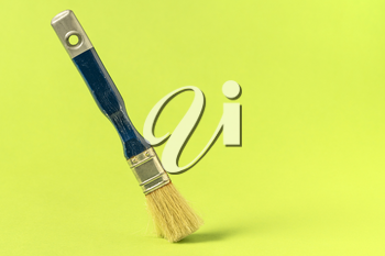 Paint brush stands on the green background, copy-space