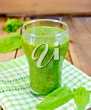 Glass cup with a cocktail of spinach, spinach leaves on a napkin on the background of wooden boards