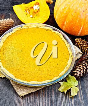 Pumpkin pie in a glass pan, pumpkin, cones and maple leaf on the background of dark wood planks