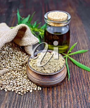 Hemp flour in a clay bowl, the grain in the bag and on the table, the oil in a glass jar, cannabis leaves on the background of wood planks