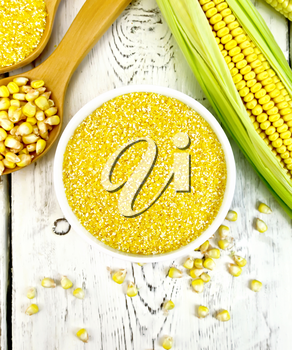 Corn grits in a bowl and spoon, cobs and grains on the background of the wooden planks on top