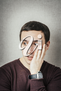 young man in shock with hands on face
