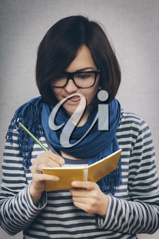 young woman in glasses writes something in a notebook