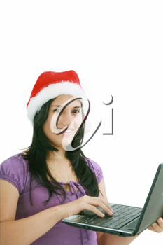 Beautiful business woman is working in office in santa claus hat