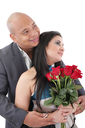 Couple holding a bouquet of red roses looking at a copyspace