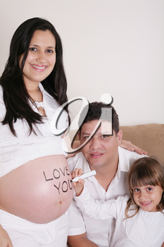 Family With Pregnant Mother Relaxing On Sofa Together with the word love you on her belly.