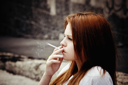 Closeup portrait of smoking beautiful young girl