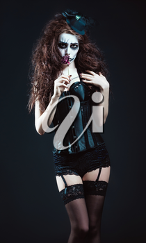 Young woman in the image of a sad gothic freak clown smelling withered flower