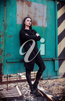 Fashion shot: portrait of the cute rock girl (informal model) in tunic and leather pants standing in industrial area