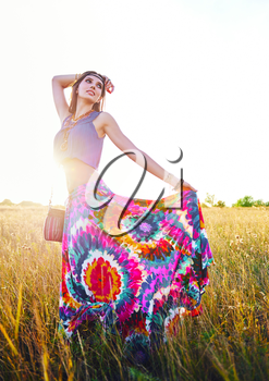 Outdoor portrait of the smiling attractive young boho (hippie) girl in meadow