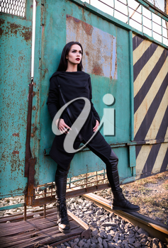 Fashion shot: portrait of the lovely rock girl (informal model) in tunic and leather pants standing at metallic gates
