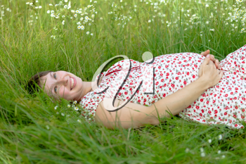 Royalty Free Photo of a Pregnant Woman Laying in Grass