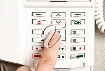Closeup of a person entering a pin code to a home alarm