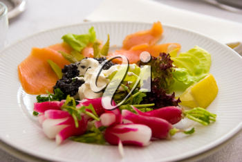 Smoked salmon with salad in a white plate