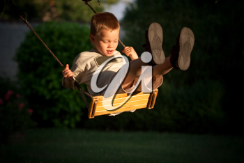 A young child playing on a swing