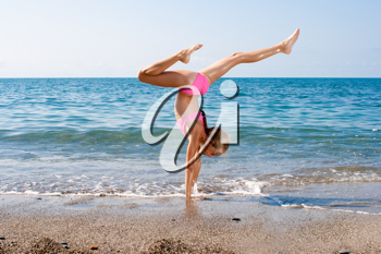 Royalty Free Photo of a Girl Doing Gymnastics at the Beach