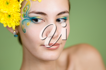 Young girl model with fantasy makeup and chrysanthemum flowers in her hair