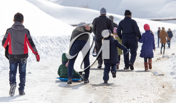 Dad and children ride baby on sled