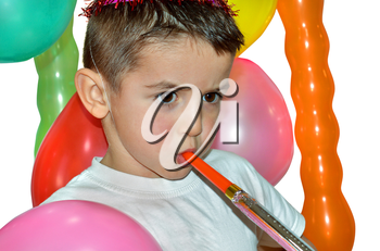 Little boy playing with air whistle and colorful balloons