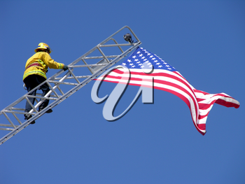 Royalty Free Photo of a Fireman Climbing a Ladder to an American Flag