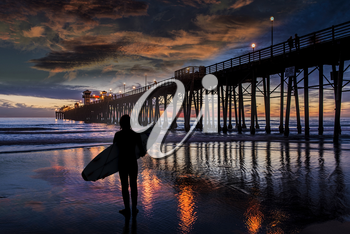 A young surfer sees nothing but flat. Oceanside Pier is silhouetted during another Southern California sunset. Oceanside is 40 miles North of San Diego, California.
