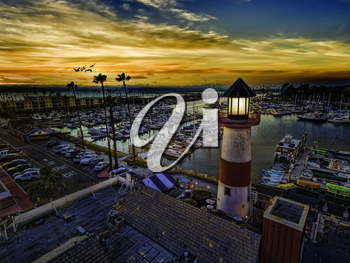 Royalty Free Photo of Pelicans gliding over the Oceanside Harbor and the little lighthouse glows. Colorful sunset in Oceanside, California, USA.