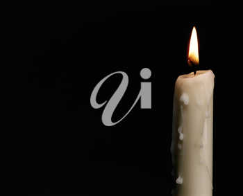 Royalty Free Photo of a Burning Candle on Black