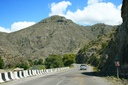 Royalty Free Photo of a Car Driving by a Mountain
