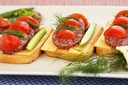 Sandwiches with salami, cheese, cherry tomato and dill on plate.