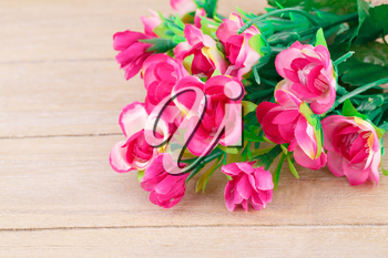 Pink artificial flowers on wooden background, closeup picture.