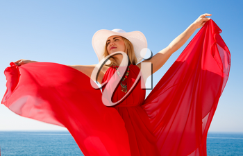 Blond woman in the red dress with the white hat at the beach in Cyprus.