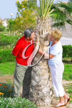 Elderly couple playfully looks at each other in tropical country.
