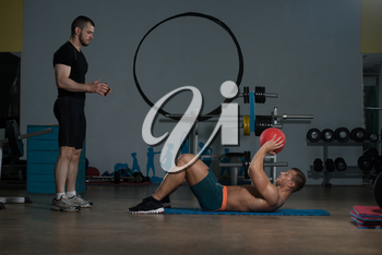 Young Man With Personal Trainer Doing Medicine Ball Exercises