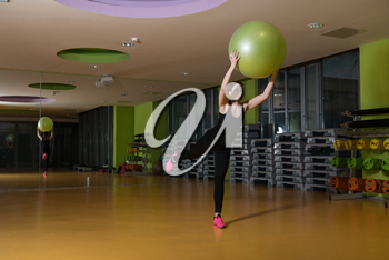 Young Woman Working Out With Ball In Fitness Center