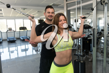 Personal Trainer Showing Young Woman How To Train Biceps On Machine In The Gym