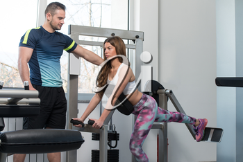 Personal Trainer Showing Young Woman How To Train Back On Machine In The Gym