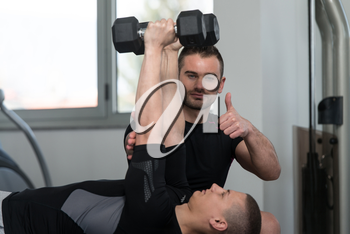 Personal Trainer Showing Ok Sign To Client - Young Man Exercising His Triceps On Machine In The Gym