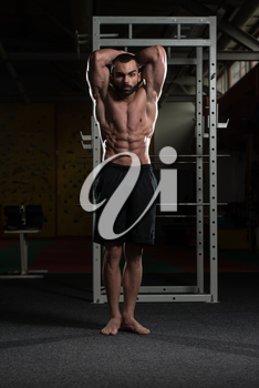 Portrait Of A Young Physically Fit Man Showing His Well Trained Abdominal Muscles - Muscular Athletic Bodybuilder Fitness Model Posing After Exercises