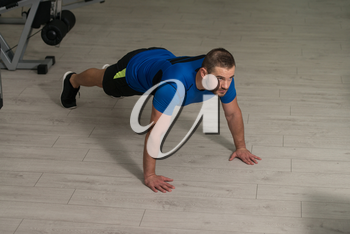Personal Trainer Doing Pushups On Floor In Gym As Part Of Bodybuilding Training