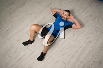 Personal Trainer Performing Abdominal Exercise On Floor - One Of The Most Effective Ab Exercises