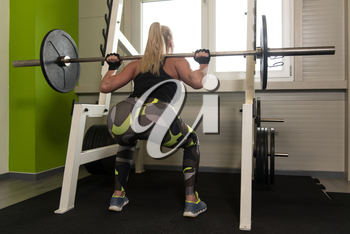 Woman Working Out Legs With Barbell In A Gym - Squat Exercise