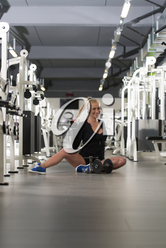 Healthy Young Woman Listening Music From His Mp3 Player In Modern Fitness Center Gym