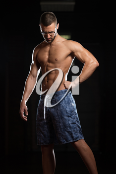 Portrait Of A Young Physically Fit Nerd Man Showing His Well Trained Body - Muscular Athletic Bodybuilder Fitness Model Posing After Exercises