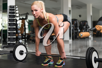 Young Woman Exercising Back With Barbell In The Gym And Flexing Muscles - Muscular Athletic Bodybuilder Fitness Model