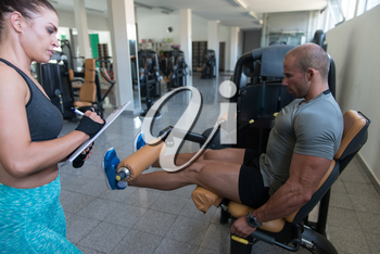 Personal Trainer Showing Young Man How To Train Legs On Machine In The Gym